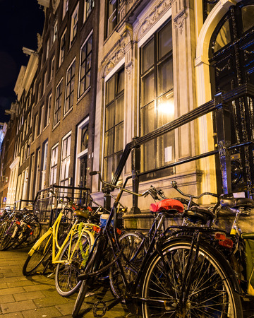 decorated bike: AMSTERDAM, NETHERLANDS - 16TH FEBRUARY 2016: Bikes changed to railings outside houses in Amsterdam at night