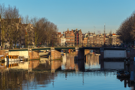 dutch canal house: AMSTERDAM, NETHERLANDS - 16TH FEBRUARY 2016: A view along the Waalseilandgracht Canal in Amsterdam at twilight. Building, boats and people can be seen.