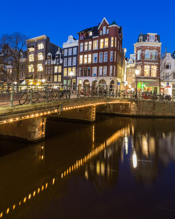 decorated bike: AMSTERDAM, NETHERLANDS - 16TH FEBRUARY 2016: A view along the Keizersgracht canal in Amsterdam at night. Buildings, bridges and bikes can be seen.