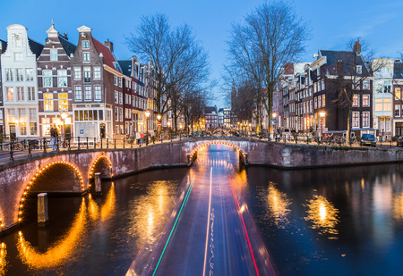 dutch canal house: A view of the bridges at the Leidsegracht and Keizersgracht canals intersection in Amsterdam at dusk. The trail from a boat can be seen.