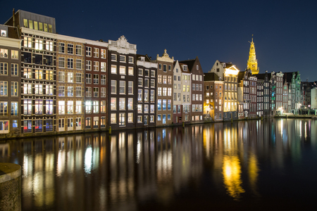 dutch canal house: Old Buildings along the Damrak in Amsterdam at night. Reflections can be seen in the water.