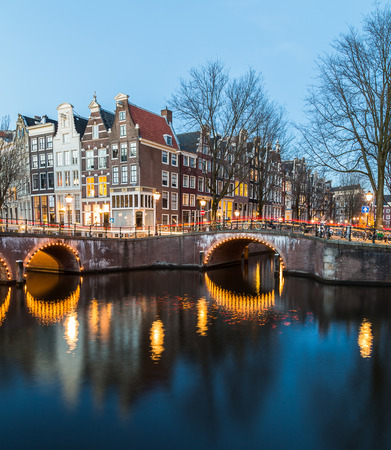 dutch canal house: A view of the bridges at the Leidsegracht and Keizersgracht canals intersection in Amsterdam at dusk. Trails from traffic can be seen on the bridge