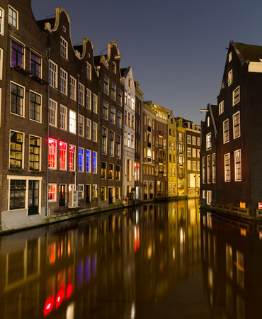 dutch canal house: A view of buildings along the canals in Amsterdam in the Centrum Borough and De Wallen Area. Taken at Night. There is space for text. Stock Photo