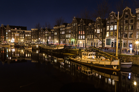 dutch canal house: AMSTERDAM, NETHERLANDS - 16TH FEBRUARY 2016: A view along the Waalseilandgracht Canal in Amsterdam at night. Building, boats and reflections can be seen. Editorial