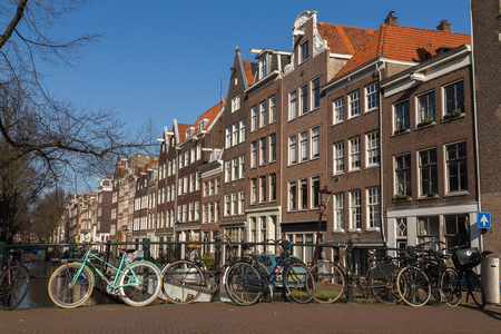 dutch canal house: AMSTERDAM, NETHERLANDS - 17TH FEBRUARY 2016: Buildings and bikes in the Centrum district of Amsterdam during the day.