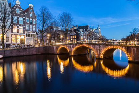 dutch canal house: A view of the bridges at the Leidsegracht and Keizersgracht canals intersection in Amsterdam at dusk. Bikes and buildings can be seen.