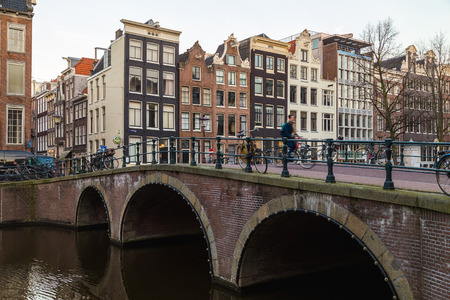 real renaissance: AMSTERDAM, NETHERLANDS - 17TH FEBRUARY 2016: Bridges and buildings in the Centrum district of Amsterdam during the morning. A cyclist can be seen.