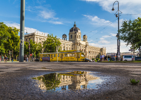 innere: VIENNA, AUSTRIA - 12TH JUNE 2016: The outside of the KH Museum in Vienna and a Yellow Ring Tram. Reflections can be seen in a puddle. People can be sen in the distance.