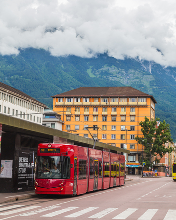 innsbruck: INNSBRUCK, AUSTRIA - 18TH JUNE 2016: Buildings and Trams in Innsbruck during the day. Low clouds can be seen.