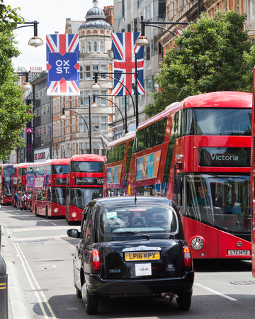 oxford street: LONDON, UK - 28TH JUNE 2016: A view along Oxford Street in London during the day. Large amounts of buses, a black London taxi and union jack flags can be seen. Editorial