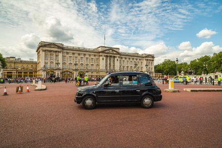 buckingham palace: LONDON, UK - 28TH JUNE 2016:  A black taxi going past Buckingham Palace during the day. Large amounts of people can be seen.