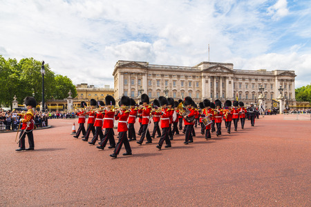 buckingham palace: LONDON, UK - 28TH JUNE 2016:  Musical support from the Regimental Band during the Changing of the Guard ceremony at Buckingham Palace in the summer.  The soldiers can be seen wearing scarlet tunics and bearskin caps