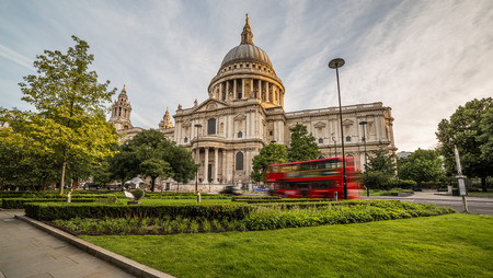 st pauls: A view of St Pauls Cathedral in central London in the morning. A red bus can be seen going past.