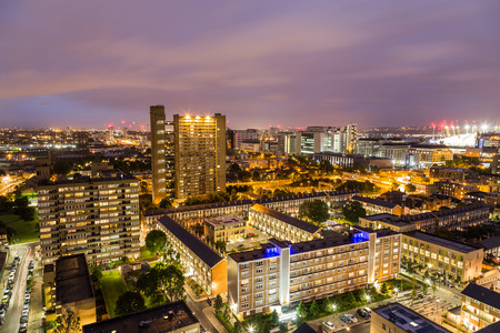 A view of apartment buildings in East London at night.