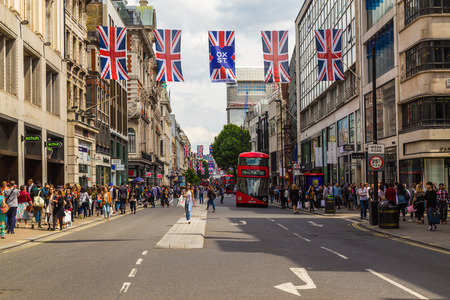 oxford street: LONDON, UK - 28TH JUNE 2016: A view along Oxford Street in London during the day. London Red double decker Buses,  union jack flags and lots of people can be seen.