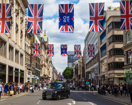 oxford street: LONDON, UK - 28TH JUNE 2016: A view along Oxford Street in London during the day. A black London taxi, union jack flags and lots of people can be seen.