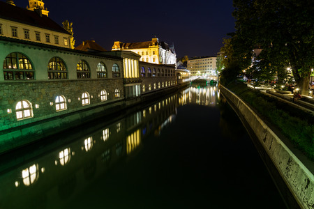 central market: LJUBLJANA, SLOVENIA - 26TH MAY 2016: The outside of  Ljubljana Central Market along the river at night. Reflections can be seen in the water Editorial