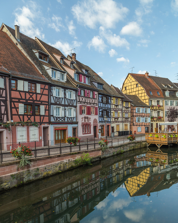 COLMAR, FRANCE - 30TH JULY 2016: A view of colourful timber framed buildings along Little Venice in Colmar during the morning. Reflections can be seen in the River Lauch