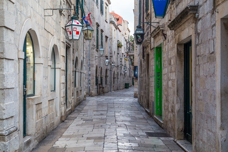 11th: DUBROVNIK, CROATIA - 11TH AUGUST 2016: A view of along quiet streets in Dubrovnik during the morning. Lamps from shops can be seen.