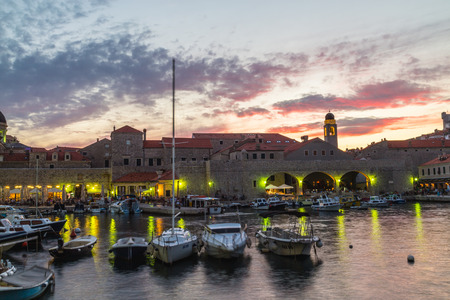 old port: DUBROVNIK, CROATIA - 11TH AUGUST 2016: Boats docked in the Dubrovnik Old Port at sunset. People can be seen. Editorial