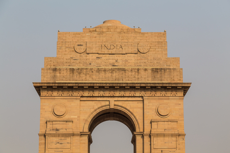 india gate: DELHI, INDIA - 19TH MARCH 2016:  A closeup to the top of the India Gate War Memorial during the day. Writing and words can be seen.