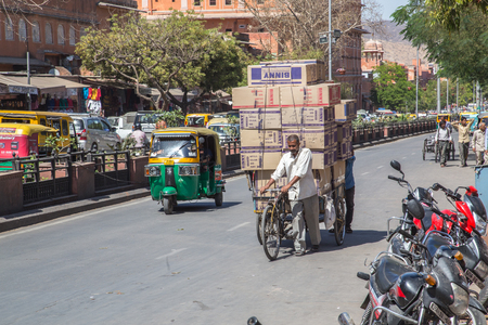 jaipur: JAIPUR, INDIA - 22ND MARCH 2016: People transporting boxes of goods on a cart in central Jaipur during the day. Editorial