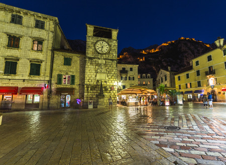 KOTOR, MONTENEGRO - 13TH AUGUST 2016: Views along streets of Old Town Kotor at night. The outside of buildings, restaurants and people can be seen.