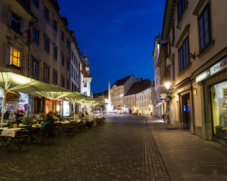 LJUBLJANA, SLOVENIA - 26TH MAY 2016: The outside of buildings and streets in Town Square Ljubljana at night. People can be seen at local restaurants and on the streets.
