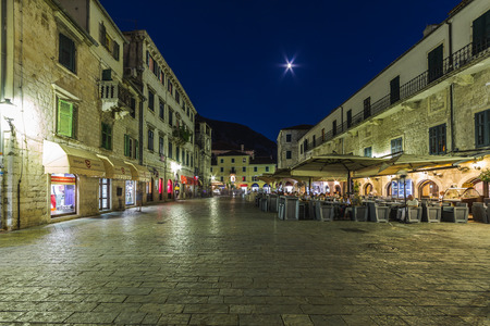 alfresco: KOTOR, MONTENEGRO - 13TH AUGUST 2016: Views along streets of Old Town Kotor at night. The outside of buildings, restaurants and people can be seen.