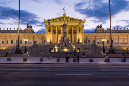 innere: VIENNA, AUSTRIA - 23RD AUGUST 2016: The outside of the Austrian Parliament at night. People can be seen outside