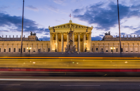 innere: The outside of the Austrian Parliament at night. A tram can be seen going past