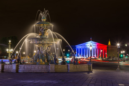PARIS, FRANCE - 28TH JULY 2016: Fontaine des Mers at night. Palais Bourbon with the French Flag illuminated on it can be seen in the distance.
