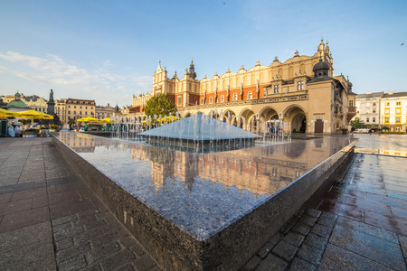 rynek: KRAKOW, POLAND -  15TH OCTOBER 2016: Architecture on Krakow Main Square in the morning. The Cloth Hall and a fountain can be seen.