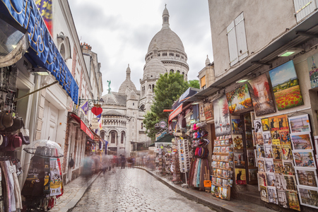 sacre coeur: PARIS, FRANCE - 28TH JULY 2016: A view along streets in Montmartre Paris during the day. The Sacre-Coer can be seen in the distance
