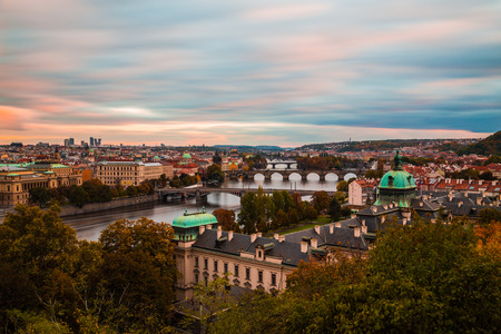 vltava river: A view of the Prague Skyline at sunset. Bridges, the Vltava river and buildings can be seen.