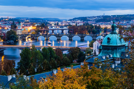 vltava river: A view of the Prague Skyline at dusk. Bridges, the Vltava river and buildings can be seen. Stock Photo