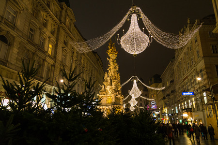 innere: VIENNA, AUSTRIA - 2ND DECEMBER 2015: A view along Graben Street at night during the Christmas season. People, decorations and buildings can be seen. The Pestsaule memorial column can be seen.