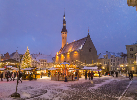 TALLINN, ESTONIA - 4TH JAN 2017: Raekoja plats, Old Town Hall Square in Tallinn at night during the festive period. Christmas decorations, market stalls and people can be seen.