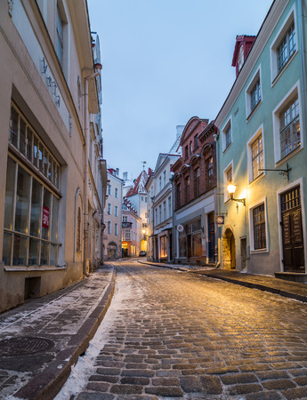lejos: TALLINN, ESTONIA - 4TH JAN 2017: A view along Pikk street in Tallinn Old Town in the morning during the winter. Snow,  restaurants and shops can be seen.