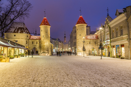 TALLINN, ESTONIA - 4TH JAN 2017: A view towards Tallinn Old Town at night during the winter. Viru Gate Towers, the tower of Tallinn Town Hall and people can be seen.
