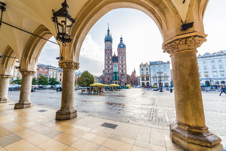 KRAKOW, POLAND -  15TH OCTOBER 2016: St. Marys Basilica, shops and buildings on Rynek Glowny (Main Square) in Krakow in the morning.