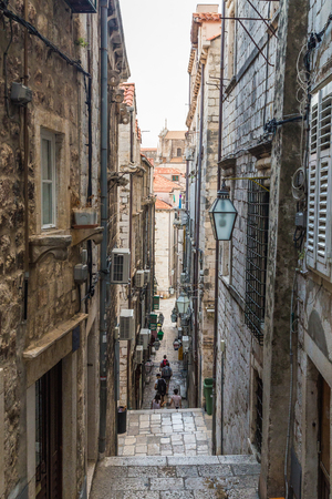 DUBROVNIK, CROATIA - 11TH AUGUST 2016: A view along narrow streets of Dubrovnik Old Town in the morning. People can be seen.