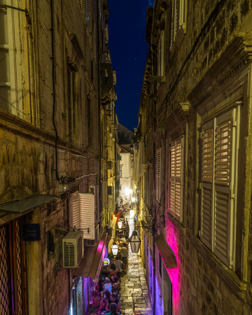 11th: DUBROVNIK, CROATIA - 11TH AUGUST 2016: A view along streets of Dubrovnik at night. People and the outside of shops can be seen. Editorial