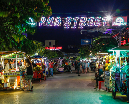 SIEM REAP, CAMBODIA - 29TH MARCH 2017: Streets in Siem Reap Cambodia at night. People, stalls and a sign for Pub Street can be seen,