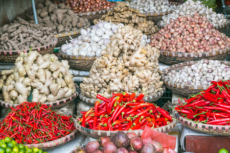 Large amounts of vegetables on display at a market in Hanoi, Vietnam. Including red peppers, chilli, garlic and ginger. Stock Photo