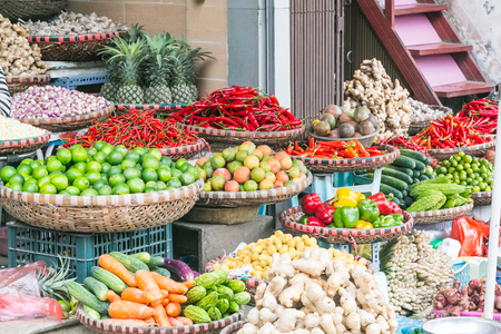 Large amounts of vegetables on display at a market in Hanoi, Vietnam. Including carrots, peppers, onions,limes and cucumbers,