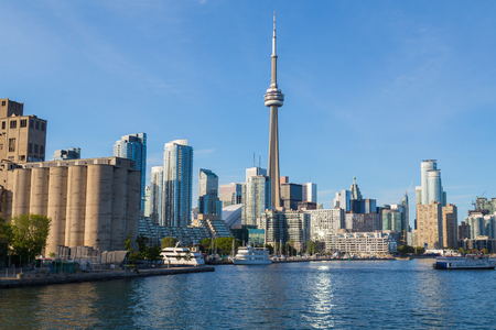 TORONTO, CANADA - 7TH JUNE 2015: The CN Tower, condos, office buildings in Toronto along the waterfront during the day. Boats can also be seen.