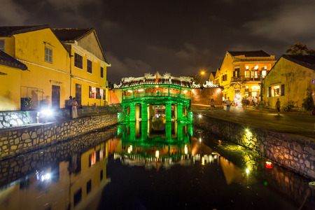 HOI AN, VIETNAM - 24TH MARCH 2017: The Old Japanese Bridge in Hoi An at night. Reflections, other buildings and people can be seen.