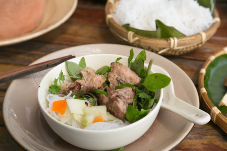 Closeup to a serving of Bun Cha in Vietnam. The meal is a popular dish in the country and consists of grilled pork, rice noodles, herbs and sauce