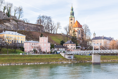 SALZBURG, AUSTRIA - 11TH DECEMBER 2015: The outside of the Pfarrkirche Mülln (Roman Catholic Parish) Church in Salzburg during the day from the River bank. Other buildings and people can be seen. Editorial